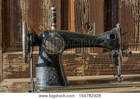 Forgotten black retro sewing machine in abandoned old house. Classic mechanical sewing machine details with old vintage wooden background.