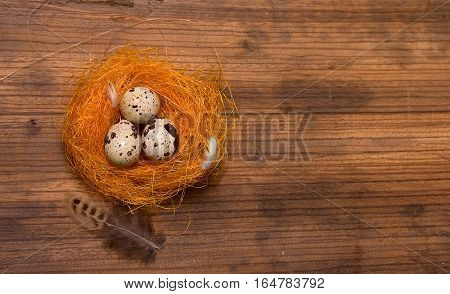 Three quail eggs in a nest of artificial straw on old wooden background