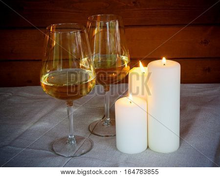 Two glasses of  white wine with candles