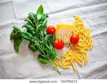 Basil tomatoes parmesan and raw pasta penne on gray tablecloth