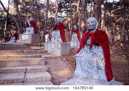 Forest with stone statues of monks wearing red mantles.