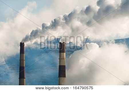 Two fuming factory chimney. Against the background of the blue sky.
