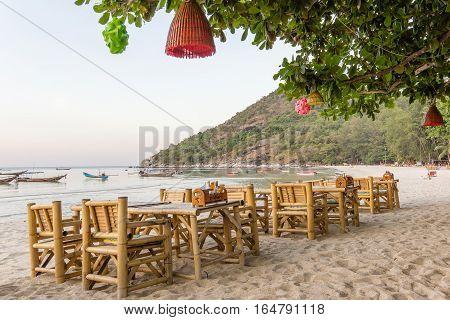Tables and chairs on a beautiful beach. Ao Thong Nai Pan Yai, Koh Pangan, Thailand. In the trees hang some lanterns.