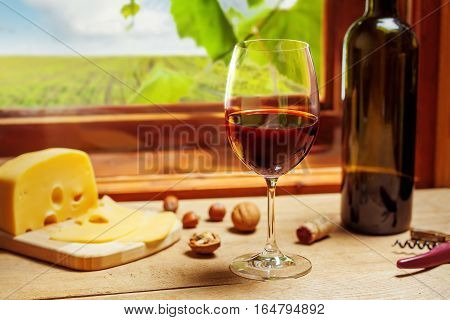 Red wine bottle and glass on wodden table
