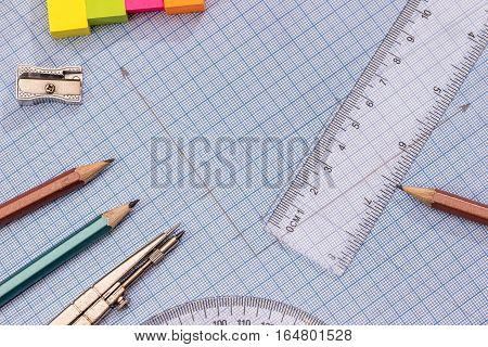 Measuring tools above blue graph paper. design