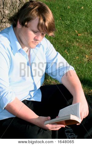 Teen Boy Reading  Outdoors