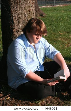 Teen Boy Reading In Park