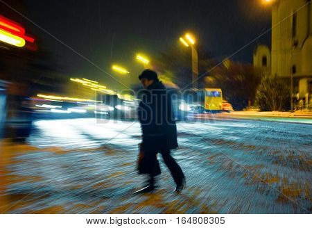 Woman on zebra crossing at night. Intentional motion blur