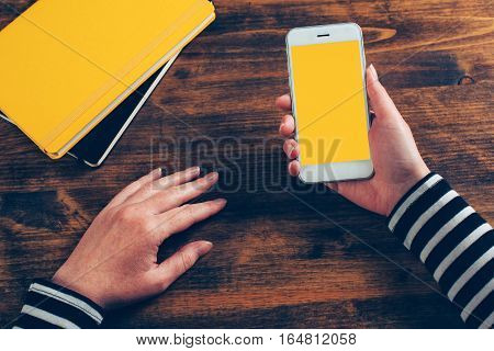Mock up of female hands using smartphone top view on office desktop