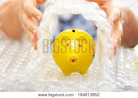 Protect your savings concept with bubble wrap covering a yellow piggy bank