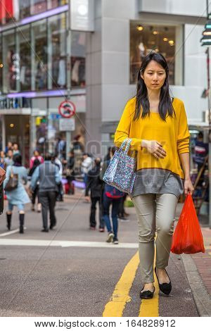 Hong Kong, China - December 6, 2016: asian nice young woman with shopping bags in street market Jardine's Crescent, Causaway Bay, shopping district, full of roadside famous brand shops.