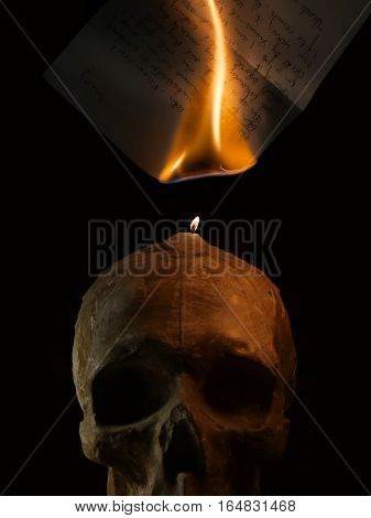 Burning handwritten letter by candle fire on skull sculpture.