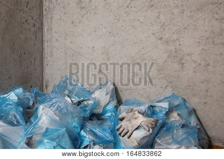 Dirty gloves employee . The repair process . Freed from the wall wallpaper . A large pile of garbage and waste in blue bags . Restoring order . Concrete wall