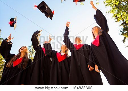 Successful Five Students With Congratulations Together Throwing Graduation Hats In The Air And Celeb