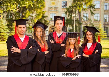 Successful Confident Five Graduates In Robes And Hats Standing In Row While Crossing Hands