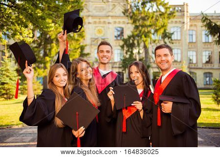 Portrait Of Happy Five Graduates In Robes Holding Mortar-board With Tassel