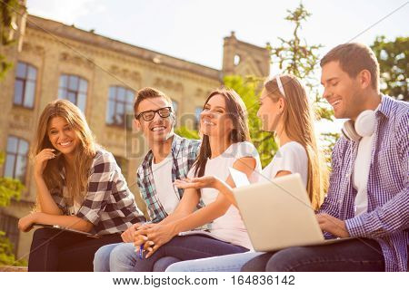 Five Happy Classmates Laughing And Sitting On Bench Near College