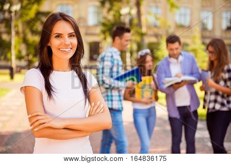 Happy Successful Pretty  Woman Crossing Hands And Smiling Near Campus With Her Friends