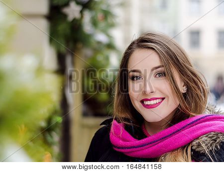 Young lady with long blonde hair and perfect makeup looking at the camera and smiling, outdoor shooting in the city. Winter look in stylish clothes. Light colors photo, close up portrait with green