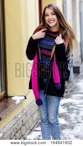Young lady with long blonde hair and perfect makeup looking at the camera and smiling, outdoor shooting in the city. Winter look in stylish clothes. Light colors photo, portrait on the street