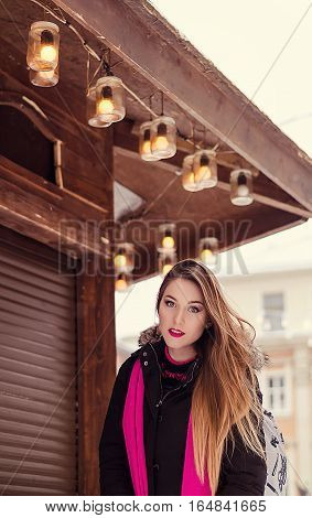 Young lady with long blonde hair and perfect makeup looking at the camera, outdoor shooting in the city. Winter look in stylish clothes. Light colors photo, portrait on the street