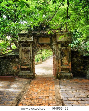 Brick Walkway To Old Stone Gate Leading Into Tropical Garden