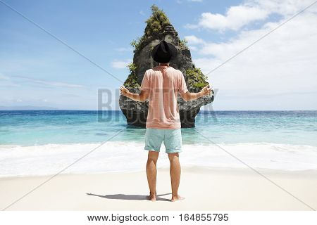 Back View Of Young Traveler In Black Hat Standing Barefooted On Sandy Beach In Front Of Rocky Cliff,
