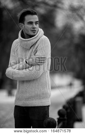 Young man in cold winter weather. He is cold and he shrank from the cold.