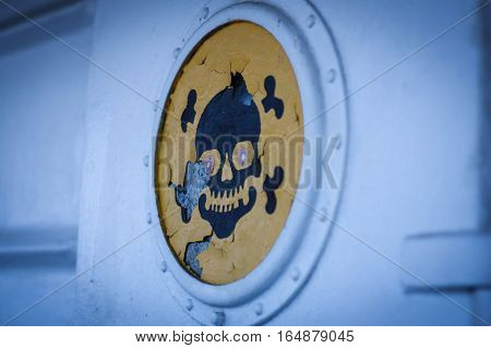 Skull and crossbones on the yellow background, shabby paint.Sign