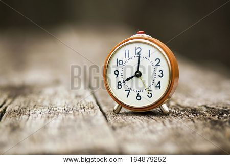 Time concept - orange alarm clock on a wooden table