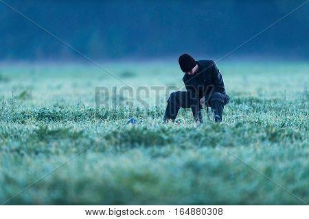 Man Sitting On Stool In Meadow On Cold Morning. Noordijkerveld. Achterhoek. Gelderland. The Netherla