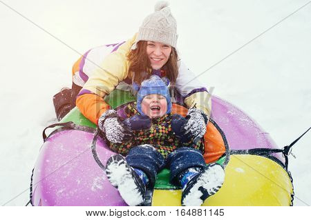 Happy smiling mother and child sitting on snow tubes. Winter vacation concept.