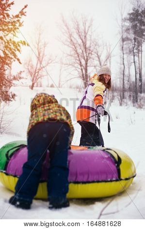 Happy smiling mother and kid sliding on snow tubing. Winter vacation concept.