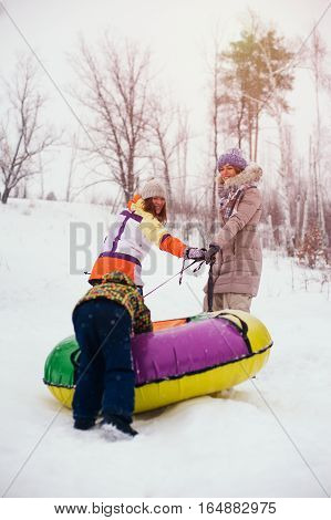 Snowtubing activity. Two smiling woman and child having fun on snow tube. Winter vacation concept.