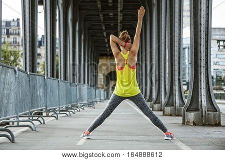 Active Woman Stretching On Pont De Bir-hakeim Bridge In Paris