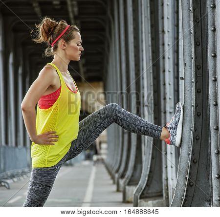 Woman Jogger Stretching On Pont De Bir-hakeim Bridge In Paris