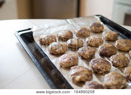 Dessert lying in rows on an iron pan. Raw chocolate dough.
