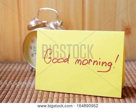 Retro alarm clock next to the paper that says good morning.