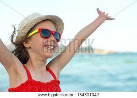 Summer vacation concept. Smiling girl with arms wide open.