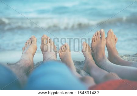 Three Pairs Of Feet On The Sand. Family On Vacations.