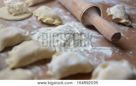 Step-by-step process of creating a home with cottage cheese dumplings. Finished products made of dough lying on the kitchen table next to rolling pin.