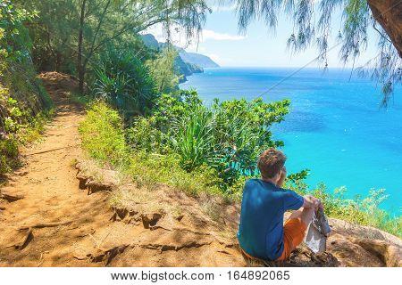 Young hiker resting in Kalalau trail, Kauai Island, Hawaii