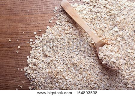 Oat flakes in the wooden spoon on the oat flakes background. Healthy eating and lifestyle.