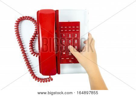 Child hand pressing number button on telephone
