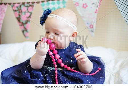 little baby girl in blue dress with pink beads.