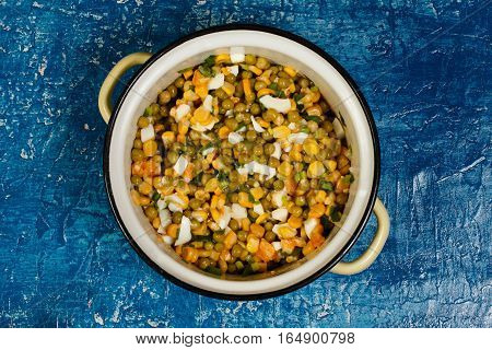 Salad of canned peas corn and eggs in the pan enamelling. On a blue textured background