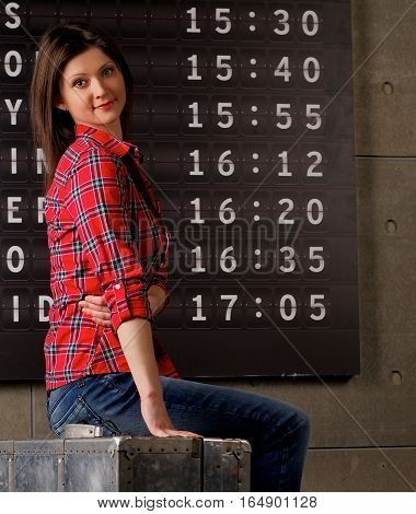 Attractive Young Woman in Checkered Shirt and Jeans Sitting on Obsolete Suitcase against Arrival Departure Board