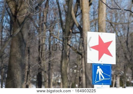 Ski trail sign with picture of skiing and red star to mark the start of path in snowy forest on sunny day for National Ski Day or for cross-country skiing and healthy outdoor winter activities
