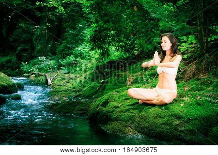 a young beautiful lady is meditating by a river flowing through the forest
