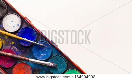 Water color pallet with two paint brushes laying on it with a white background